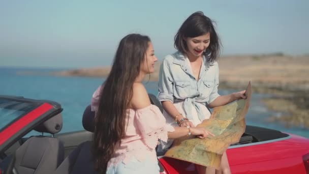 Two fancy girls on cabriolet exploring the map. Travel, lifestyle. luxury, freedom, blogging concept. Filmed on Sony, 4k, 10 bit color