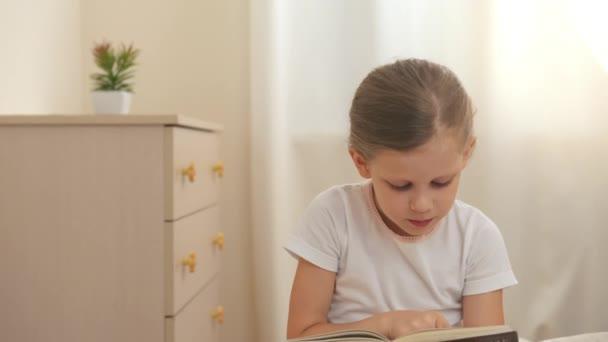 Rozkošná holčička drží příběh knihy, sedí na posteli a čtení