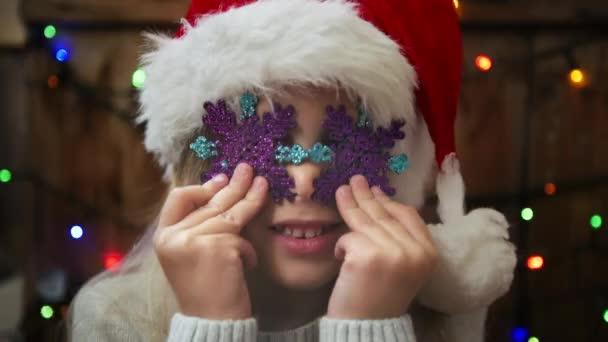 Niedliche Mädchen Holding Schneeflocken. Hübsches Kind in Nikolausmütze Spaß an Weihnachten