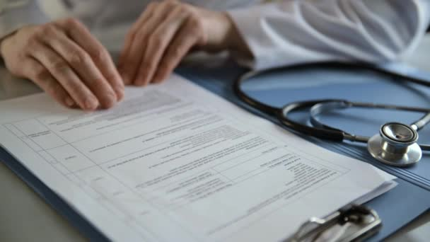 Close-up of female doctor studying medical history of patient in her office.