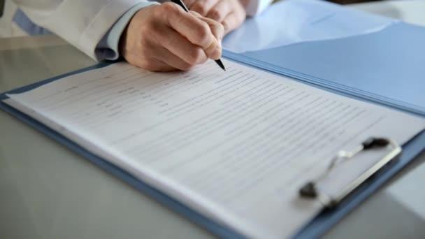 Therapeutin schreibt Arztbericht am Schreibtisch in Klinik.