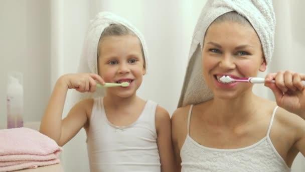 Radostné dítě s její matkou, čištění zubů po koupeli. Koncepce péče o zuby a hygieny.