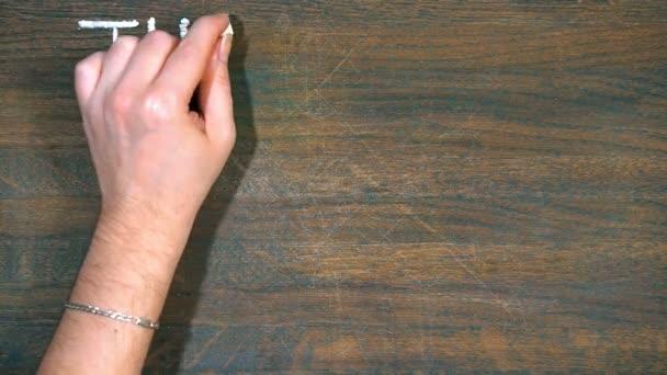 Vielen Dank. Nahaufnahme der Hand zeichnet auf einem Holzbrett. Lächeln und Inschrift mit Kreide.