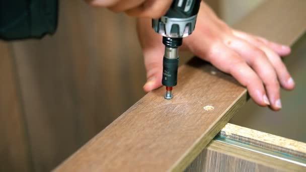 Upevnění panelu pomocí šroub šroubovákem. Ruční šroubovák ve svislé poloze. nábytek