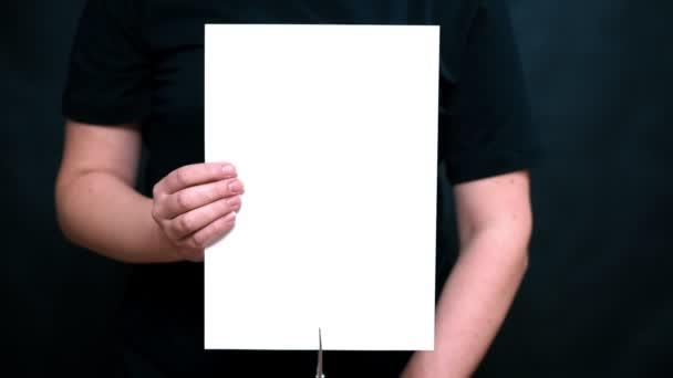 Detailní záběr rukou s listem papíru na barvy pozadí. Nůžkové list bílého papíru podélně.