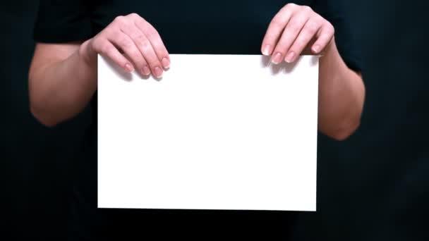 Detailní záběr rukou s listem papíru na barvy pozadí. Rukou roztrhat list bílého papíru přes