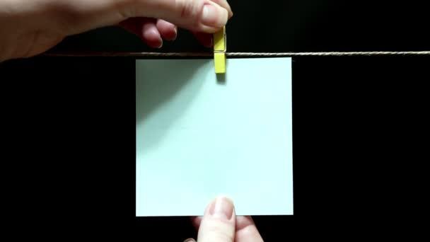Kopírovat prostoru. Čistě bílá nálepka. List je ručně připojena s clothespin na laně.