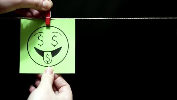 zwei Aufkleber. Emotionen. auf dem grünen rechten Blatt auf dem Gesichtsausdruck Liebe zum Geld. auf der blauen Seite im Gesicht ein Ausdruck der Enttäuschung und Traurigkeit.
