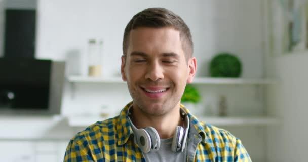 Portrét mladého šťastného muže, který měl na krku bezdrátovou náhlavní soupravu