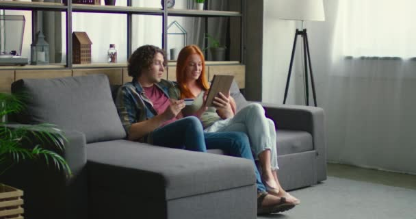 Young beautiful couple is doing online shopping in living room