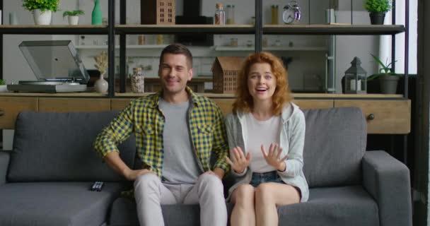 junges Paar schaut sich Sportspiele an, sitzt auf dem Sofa und feiert sein Tor