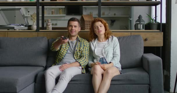 Young man and woman are looking for something to watch on TV