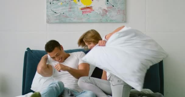 Young mixed couple start a pillow fight in bedroom