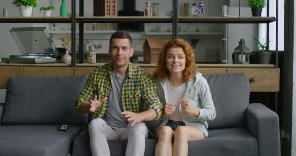 Junges Paar feiert sein Tor, sitzt zu Hause auf dem Sofa