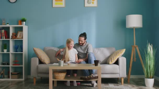 Dad and His Small Daughter Have Fun While Reading Book