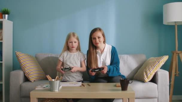 Kleines Mädchen spielt Videospiel mit Mama
