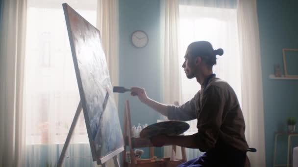 Inspirierter junger Mann malt auf Leinwand
