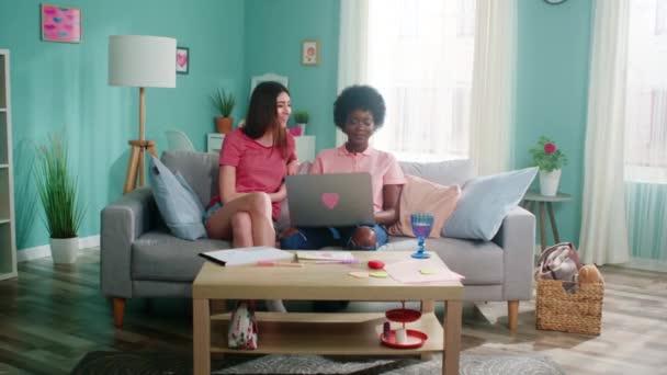 Hübsche Frauen sitzen auf Sofa und benutzen Laptop
