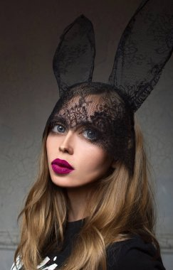 portrait of disproportionate, modern, stylish, fashionable sad woman after plastic surgery or after filters in photo edit application in bunny lace ears