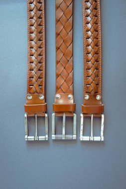 three leather brown belts on grey paper background