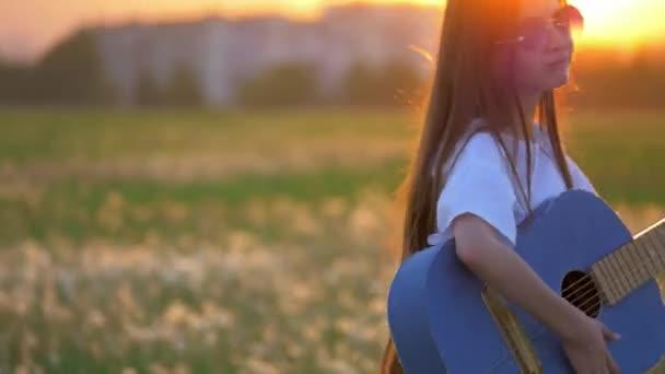 zblízka legrační malá holka kluk hraje na kytaru v poli pampelišky při západu slunce. venku mimo město budovy emoce a zábavnější grimasy karikaturu popová hvězda
