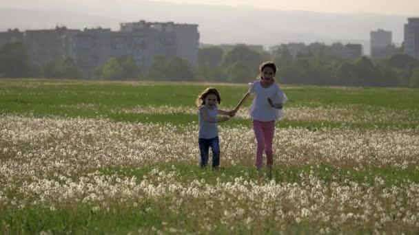 Sestry, běží v oboru pampelišky a směje se šťastné dětství. koncept svobody a zábava