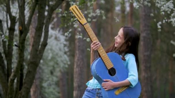 Dvě děti dívky se baví hrát blue kytara s dlouhými blonďatými vlasy, vrtěla hlavou na Park. Jarní nálada usmívá smích radost