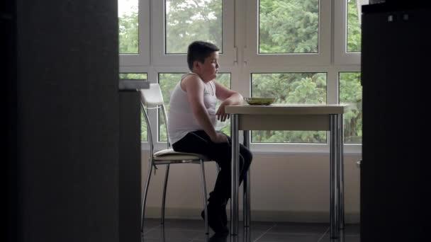 vastag kisfiú ül a konyha asztalnál, a háttérben ablak, a koncepció a gyermekkori elhízás és a torkosság a lemez élelmiszer-nézett
