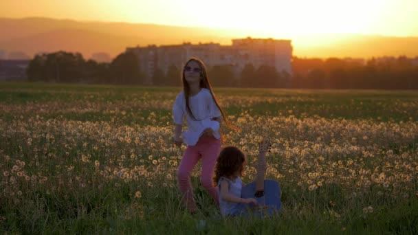 Két kis örömteli nővérek szórakozni a szabadban játszani a gitár táncol és ugrál a szabadban. pitypang mezőben, naplemente, esti órákban, boldog childhood.concept szabadság és szórakozás a városban.