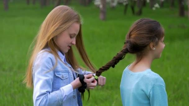 hezká mladá holčička plisé COP její přítelkyni. Pletení copánků na hlavu.