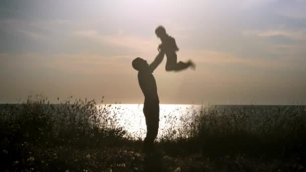 silueta otce a syna baví na pláži při západu slunce, táta zvrací mladík do vzduchu