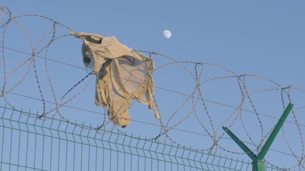 zblízka kus oblečení visí ostnatý drát plot chráněné oblasti. větrné počasí vysoký plot vězení teritorium koncept vězení útěk svobodu a trest odnětí svobody.