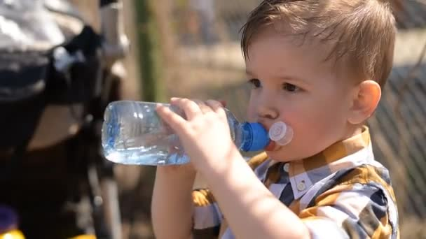 handsome boy drinks clear water from a bottle on a sunny day outside