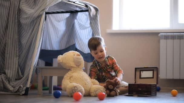 malý chlapec postavil ve svém pokoji vigvamu a tam si hraje s medvídkem