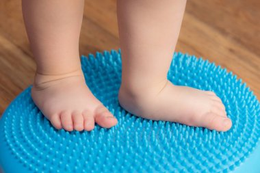 little kid massages his feet while standing on the rug