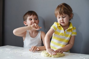 Little cheerful children make shortbread. Rolls out the dough with a rolling pin on a white table. The preparation of the dessert.