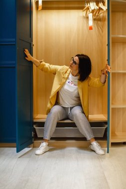 The concept of choice. The girl chooses a large, roomy closet in a furniture store. Sitting in the closet