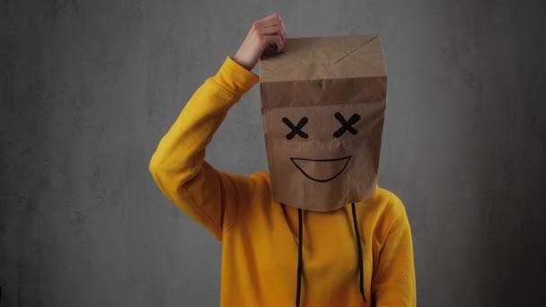 osoba s papírovými sáčky na hlavě, s pomalovanou emotipoje, úsměv škrábance na hlavě.