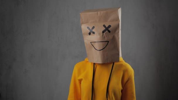 dívku s papírovými pytlíky na hlavě s pomalovanou emotiškou, úsměv. 4k