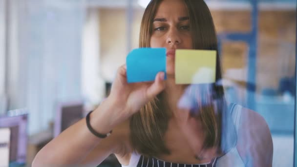 Front view close up of pretty woman executive adding colorful sticky notes on glass in modern office