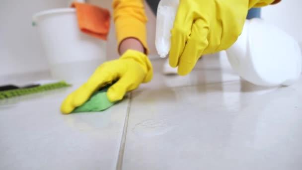Žena v domácnosti se žlutými rukavicemi se snaží čistit bílou podlahu s pěnou a houbou, zblízka, úklid