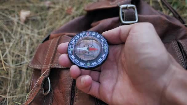 Caucasian traveler sits, relaxes, and is guided by a compass, hands close-up 4k