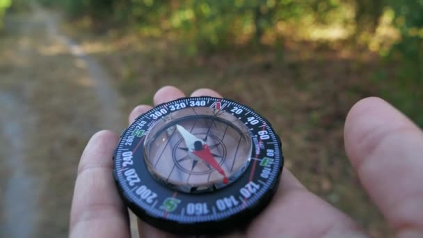 Extreme close-up of a transparent modern compas in the forest background. Concept of travel, adventure, expedition