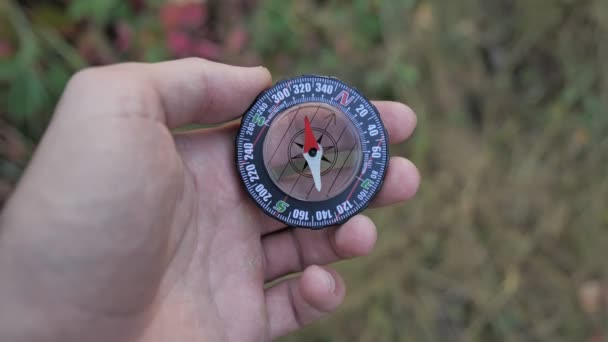 close up a male tourist holds glass compass in his hands while in the forest 4k