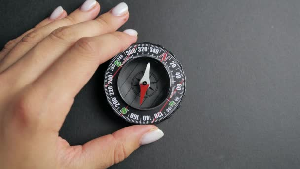 close up compass with moving needle on top on black background
