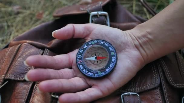 Female hands holding compass and looking for direction of North. Orientation in forest