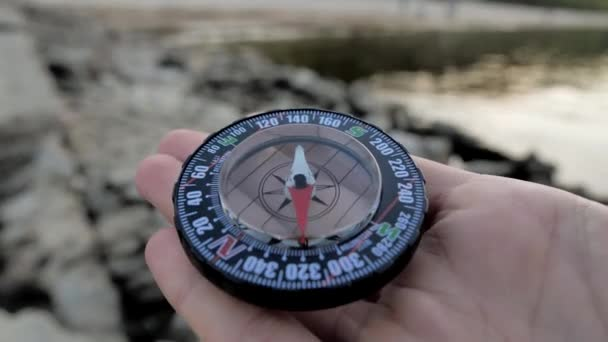 Tourist compass on the hand using a compass on the stone beach with nature coast 4k