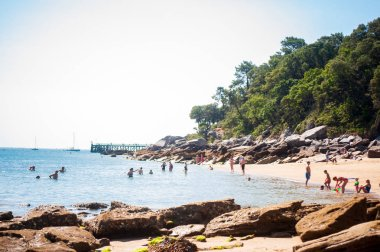 View on the beach of l' Anse Rouge at summertime with a lot of people on it
