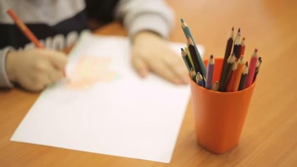 Egy fiú felhívja a rajz színes ceruzák