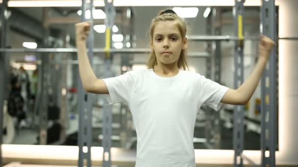 Little girl looks at her muscles